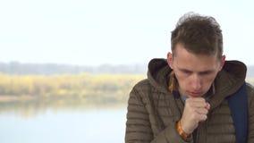 De Kaukasische knappe zekere 25s-kerel in jasje openlucht hoest stock video