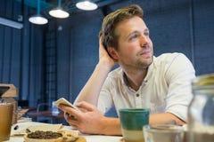 De Kaukasische man in de koffie die op zijn vrienden wachten Stock Foto