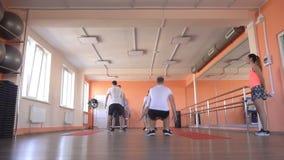 De Kaukasische mannelijke vrienden spelen sporten in een modern fitness centrum met behulp van een mooie meisjess trainer Groepsg stock video