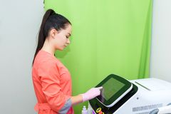 De Kaukasische meisjesschoonheidsspecialist past het apparaat haarverwijdering met aan een laser Kosmetisch materiaalapparaat stock afbeeldingen