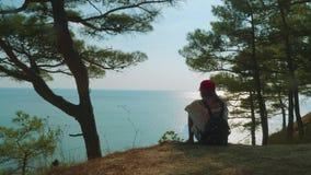 De Kaukasische meisjestiener bekijkt kalme overzees van hoge kust in zonnig weer Achter mening stock video
