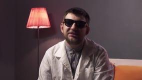 De Kaukasische mens met baard die zonnebril en witte laboratoriumlaag dragen verklaart materiaal stock videobeelden