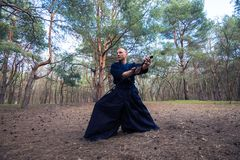 De Kaukasische mens met een katana oefent vechtsporten uit Stock Foto's