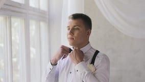 De Kaukasische mens met een kort kapsel verbetert een vlinderdas dichtbij het venster in de studio De bruidegom in een wit overhe stock footage