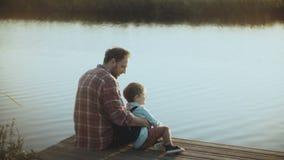 De Kaukasische mens met weinig jongen zit op een meerpijler Vader en Zoon samen Gelukkige verhouding Het grootbrengen van kindere stock videobeelden