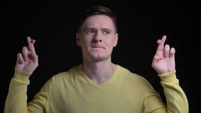 De Kaukasische mens op middelbare leeftijd in gele sweater gesturing kruisen-vingers ondertekent om hoop in camera op zwarte acht stock videobeelden