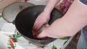 De Kaukasische mens zet op de bodem van grote ketelstukken van schaapvet Begin kokend pilau stock video