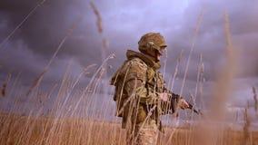 De Kaukasische militair die in motie door tarwegebied lopen, het dragen camoufleert en helm met wapen in wapens, het kijken stock videobeelden