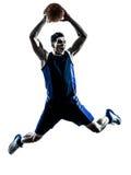 De Kaukasische speler die van het mensenbasketbal onderdompelend silhouet springen stock foto's