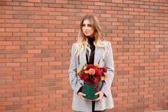 De Kaukasische vrouw status op de straat dichtbij storefront winkelt vensters houdend bloem-doos met gelukkige glimlach stock foto's
