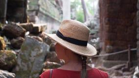 De Kaukasische vrouw in strohoed loopt onder ruïnes van Ta Prohm stock video
