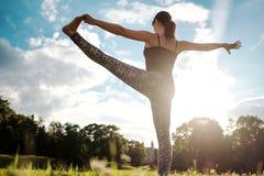 De Kaukasische vrouw in yoga bevindend saldo Utthita Hasta Padangusthasana stelt Achter mening stock fotografie
