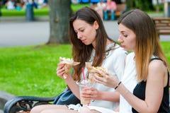 De Kaukasische vrouwen eet de sandwich van het hamburger snelle voedsel in openlucht op de straat Actieve meisjes die hongerig en Stock Foto
