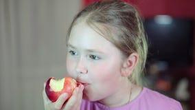 De Kaukasische witte baby eet een nectarine en het glimlachen bij de camera 4K stock footage