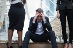 De Kaukasische zakenman zit op de treden en zijn handen clasped hoofd, het gevoel van beklemtoond, droefheid of ongenoegen stock foto's