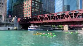 De Kayakerspeddel onderaan de Rivier van Chicago als reisboten en watertaxis vervoeren toeristen en forenzen stock footage