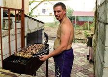 De kebabs van een jonge mensengebraden gerechten op de grill stock fotografie