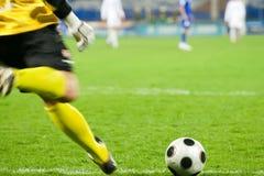 De keeper van het voetbal schopt de bal Stock Foto