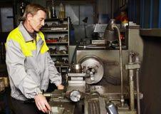 De keerder verwerkt metaalwerkstuk bij het draaien van draaibank Stock Foto's