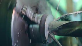 De keerder werkt aan een draaiende draaibank bij de fabriek van de metaalbouw stock videobeelden