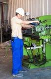De werktuigkundige werkt bij de draaibank bij fabriek stock foto