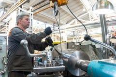 De keerderarbeider beheert het metaalbewerkende proces van mechanisch knipsel op een draaibank stock fotografie