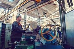De keerderarbeider beheert het metaalbewerkende proces van mechanisch knipsel op een draaibank royalty-vrije stock foto