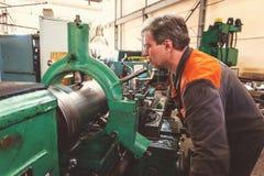 De keerderarbeider beheert het metaalbewerkende proces van mechanisch knipsel op een draaibank royalty-vrije stock foto's