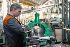 De keerderarbeider beheert het metaalbewerkende proces van mechanisch knipsel op een draaibank stock afbeelding