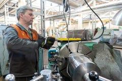 De keerderarbeider beheert het metaalbewerkende proces van mechanisch knipsel op een draaibank royalty-vrije stock afbeelding