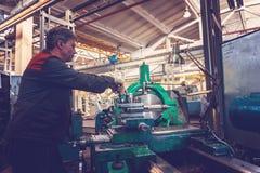 De keerderarbeider beheert het metaalbewerkende proces van mechanisch knipsel op een draaibank royalty-vrije stock afbeeldingen
