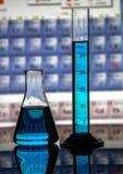 De kegelfles van het chemielaboratorium en metende cilinder op een nadenkende oppervlakte en een periodieke lijstachtergrond stock afbeeldingen