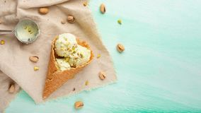 De kegels van het pistacheroomijs met pistaches en een lepel voor roomijs Op een muntachtergrond Vlak leg royalty-vrije stock foto