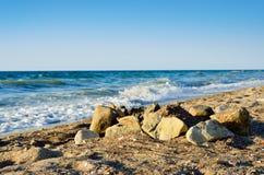 De keien op het strand, tegen getijde droegen van het overzees stock fotografie