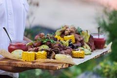 De kelner biedt geroosterde vlees en groenten aan royalty-vrije stock afbeeldingen