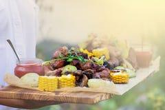 De kelner biedt geroosterde vlees en groenten bij zonnige dag aan stock afbeeldingen