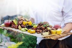 De kelner biedt geroosterde vlees en groenten bij zonnige dag aan stock foto