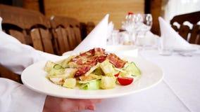 De kelner brengt een schotel met salade in het restaurant zet op een plaat met een wit tafelkleed, een bestek en schotels wordt b stock videobeelden