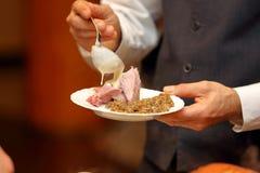 De kelner dient gedeelten van voedsel bij een partij Stock Afbeeldingen