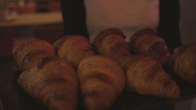 De kelner draagt dienblad met verse croissants stock video
