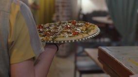De kelner draagt een grote smakelijke smakelijke ronde pizza aan de cliënt stock footage