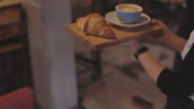 De kelner draagt koffie en croissant aan lijst bij koffie stock videobeelden