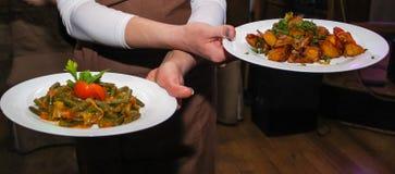 De kelner draagt schotels met aardappels, vlees, salade en saus stock foto