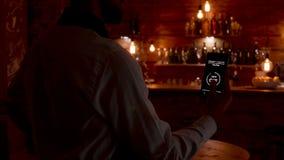 De kelner geeft een spraakopdracht aan smartphone om de lichten aan te zetten stock footage