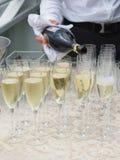De kelner giet champagne in glazen Royalty-vrije Stock Afbeelding