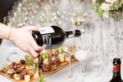 De kelner giet de champagne in de glazen Het hoogtepunt van de lijstbovenkant van glazen fonkelende witte wijn met flessen in Royalty-vrije Stock Foto's