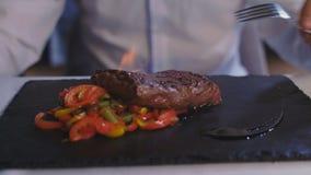De kelner giet een lapje vleeslikeur en plaatst brand aan de bezoeker van het restaurant stock footage