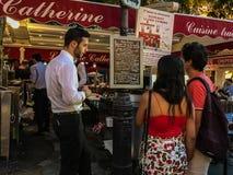 De kelner hangt terwijl het paar menu bij Montmartre-restaurant bestudeert Stock Foto
