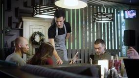 De kelner neemt orde van groep vrienden in koffie stock video