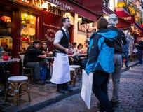 De kelner nodigt paar in zijn restaurant op Montmartre in Parijs uit Stock Foto's